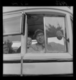 An unidentified man [bus driver? teacher?] with an unidentified pupil from Ngaio School, Wellington, looking out of a bus on a trip to Matamata