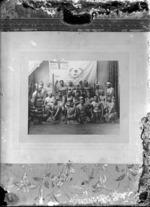 Maori men alongside a Moutoa flag