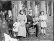 Family portrait under gum trees, unidentified parents with young son and two daughters with dolls, baby girl on father's knee, wooden building and people beyond.