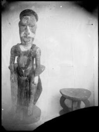Carved figure beside low carved stool, Rabaul, New Guinea, ca. 1929 / Sarah Chinnery