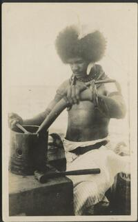 [Native boy, working on a large piston from an engine, the connecting rod is being held and he is tightening/loosening the gudgeon pin with a shifting spanner, Port Moresby, about 1925] Gibson