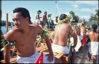 Group of men wearing white lava lava on boat