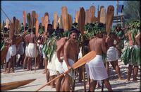 Groups of men in white lava lava holding wooden paddles