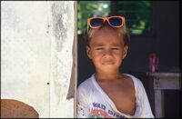 Child wearing pink framed sunglasses