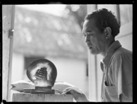 Unidentified local man with a ship carved on a shell, includes a carved fish, Rarotonga, Cook Islands