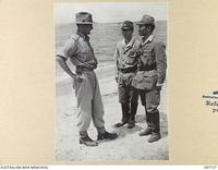 KAHILI, BOUGAINVILLE. 1945-10-02. LIEUTENANT COLONEL C.W. COURT, HEADQUARTERS 2 CORPS, TALKING WITH JAPANESE LIAISON OFFICERS AT THE AUSTRALIAN SURRENDER COMMISSION, HEADQUARTERS, KAHAILIL. ..