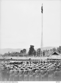 RABAUL, NEW BRITAIN. 1945-10-10. MAJOR GENERAL K.W. EATHER, GENERAL OFFICER COMMANDING 11 DIVISION, AND MEMBERS OF THE CHINESE ARMY SALUTING THE FLAG AS THE BAND PLAYS GOD SAVE THE ING. A SPECIAL ..