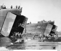 LAE AREA, NEW GUINEA. 1943. AUSTRALIAN TROOPS DISEMBARKING FROM AMERICAN LANDING SHIPS, TANK (LST), INCLUDING LST-456, EAST OF LAE IN PREPARATION FOR THE ASSAULT ON THAT TOWN. 20 MM OERLIKON AA ..