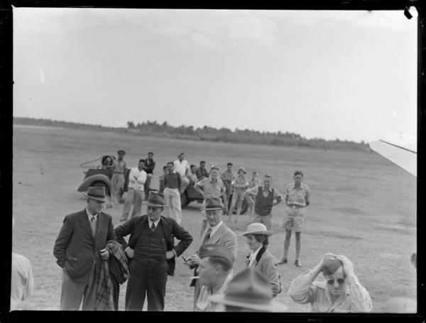 View of unidentified passengers in front of a transport plane with locals and military personnel looking on at [Fua'Amotu?] Airfield, Tonga