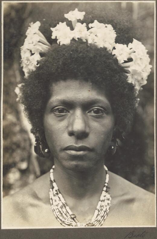 Bioto [close up of woman's face with flowers in her hair and a bead necklace] Frank Hurley