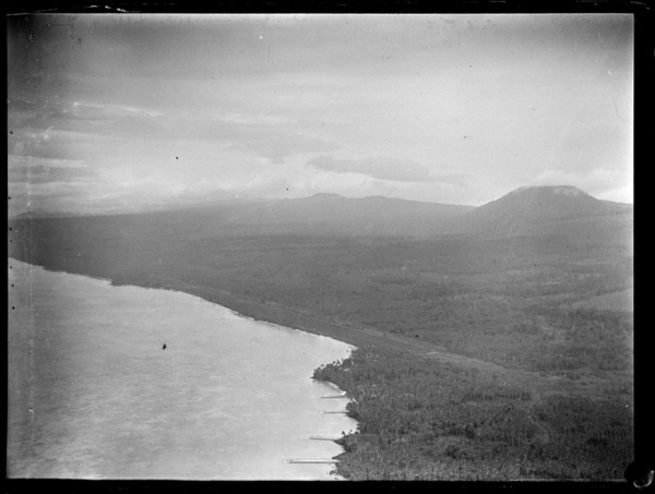 An aerial view of a coast airfield amongst palm trees near a village with beach slipways or piers, with forested mountains beyond, American Samoa