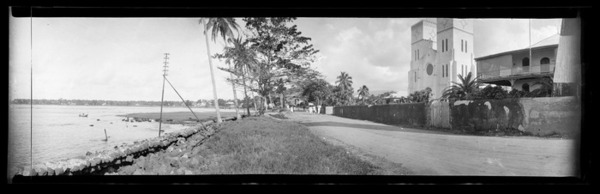 View in Samoa [probably near Apia], showing a straight road at the edge of a beach