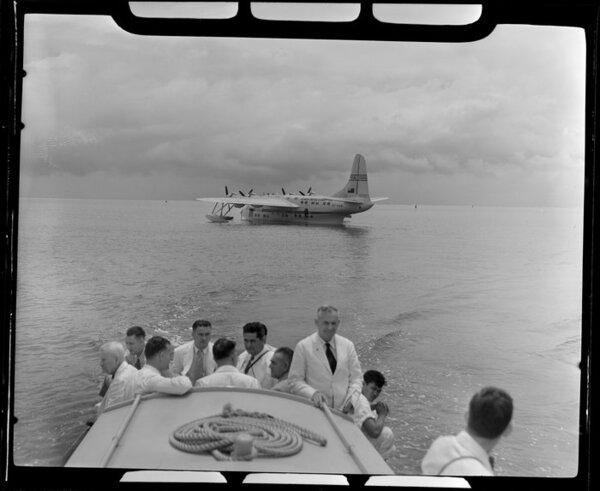 TEAL (Tasman Empire Airways Limited) ZK-AMM flying boat in background as unidentified passengers head to shore in Samoa