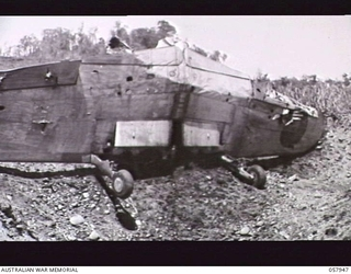 LAE, NEW GUINEA. 1943-10-04. REMAINS OF A JAPANESE ZERO FIGHTER AIRCRAFT WINGS AND LANDING GEAR IN A SHELL HOLE ON THE AIRSTRIP
