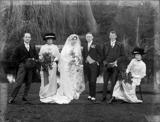 An outdoors wedding party, including bridesmaids, probably in Christchurch. Taken in 1913 by Steffano Francis Webb.