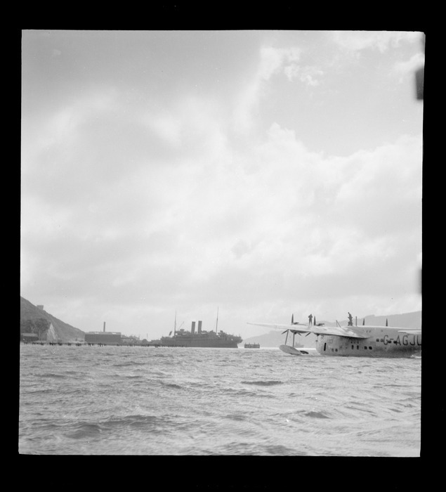 The arrival of the BOAC Hobart G-AGJL, a Short Hythe flying boat, at Evans Bay wharves with a large steamship beyond, Wellington Harbour