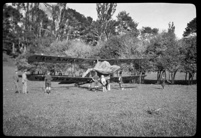 NZ Air Transport Company DH9 aeroplane, D3139, in a field at the foot of One Tree Hill, Auckland, after 'Creamoata' flight from Invercargill, sponsored by Fleming and Company, showing children inspecting the aircraft. Ref: WA-05263-F.