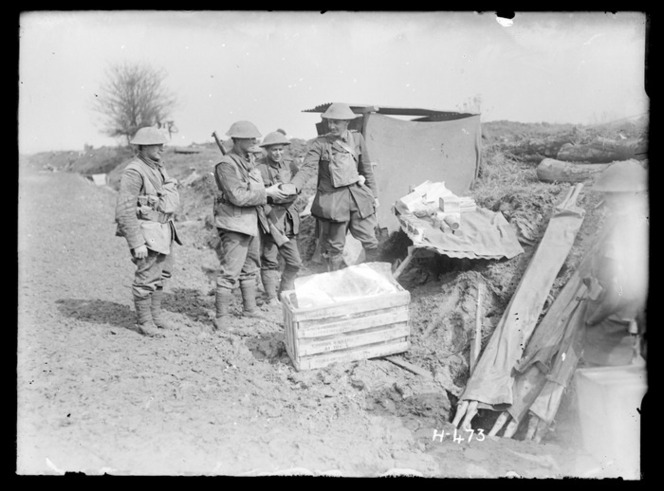 The Padre of the New Zealand Rifle Brigade operating a makeshift wayside canteen for soldiers in the front line. Shows him handing a cake to a soldier. Stretchers are prominent in the right foreground.