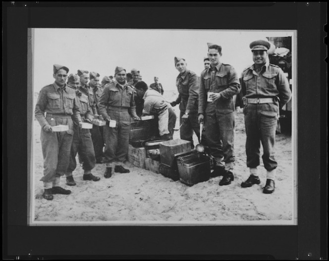Members of 28 (Maori) Battalion getting Christmas Dinner at Headquarters, Nofilia, Libya - Photograph taken by Dr C N D'Arcy