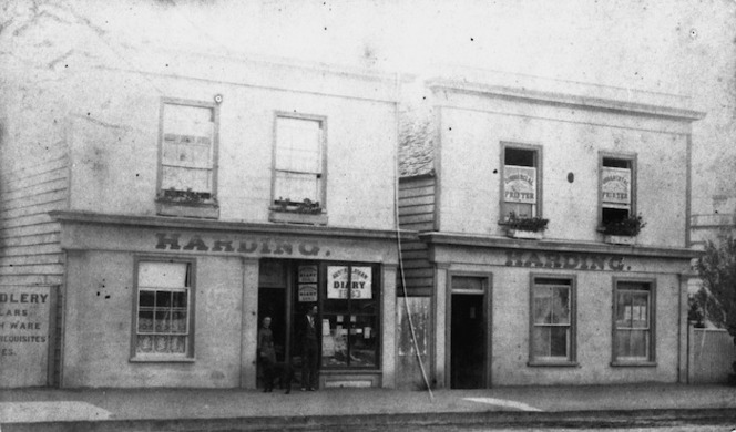 A couple and a dog stand in the doorway to the premises of Robert Coupland Harding's printing business, on Hastings Street, Napier, in 1883. An advertisement for the 'Australasian Diary 1883' is visible in the window. There are flowers in window boxes on the second storey windows.