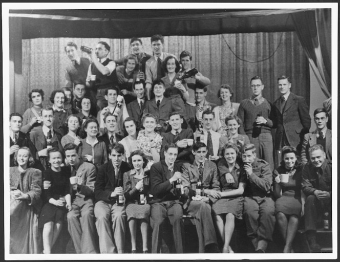 Ngaio Marsh (with beret) stands centre; Douglas Lilburn is third from the right (holding bottle). Identified as the cast of Othello (1944). Ref: PAColl-0285-1-072