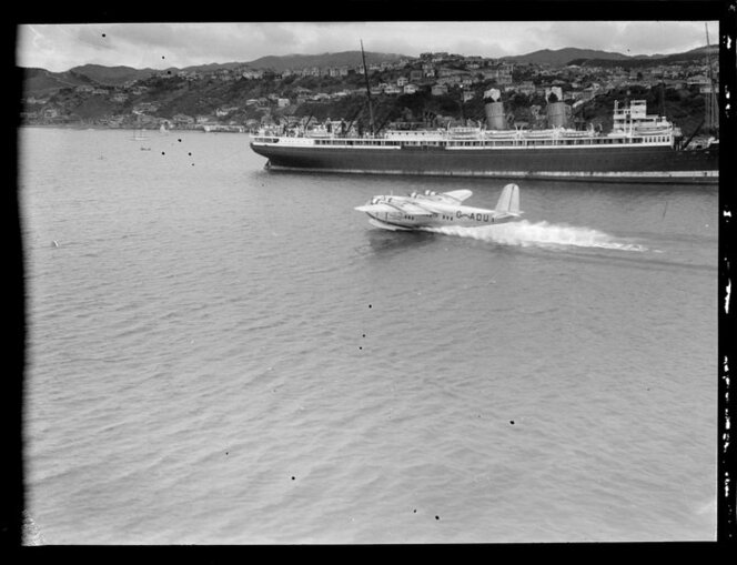 Flying boat, Centaurus, taxiing past an unidentified ship, Wellington Harbour