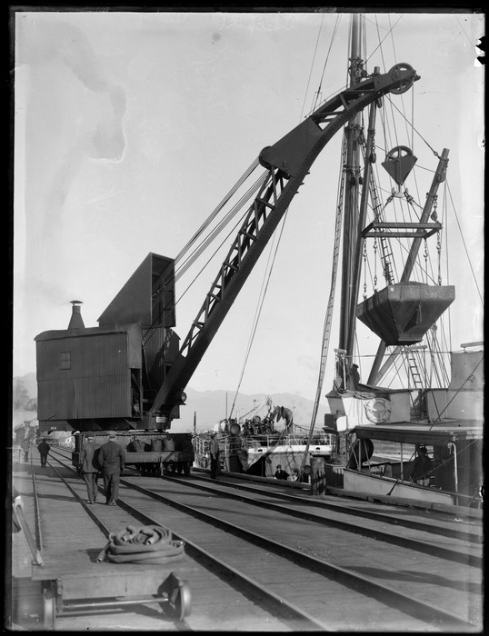 Wharf area, Westport, with crane on rails lifting coal hopper, ship and Westport Harbour beyond