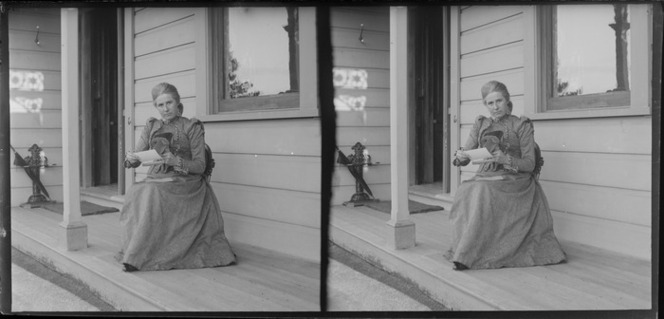 Lydia Williams sitting on a verandah holding a stereoscope and stereographic cards