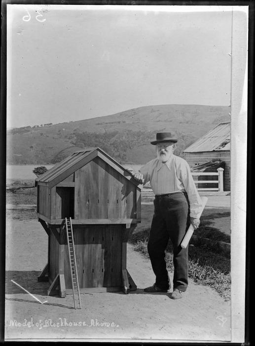 Claude Jean-Baptiste Eteveneaux standing next to a model of a blockhouse, Akaroa, Canterbury - Photograph taken by Jessie Buckland