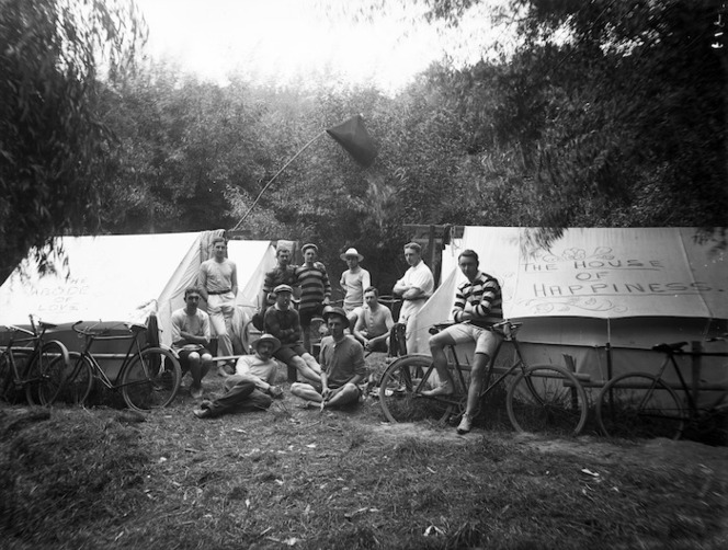 Camping scene showing a group of young men next to two tents
