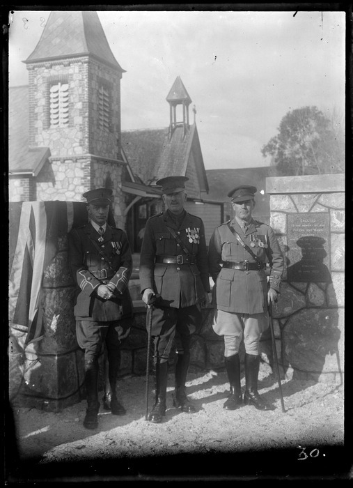 Army Officers in full military uniforms with medals and flag, outside a church with monument to fallen local WWI soldiers, Pakipaki, Hawke's Bay District