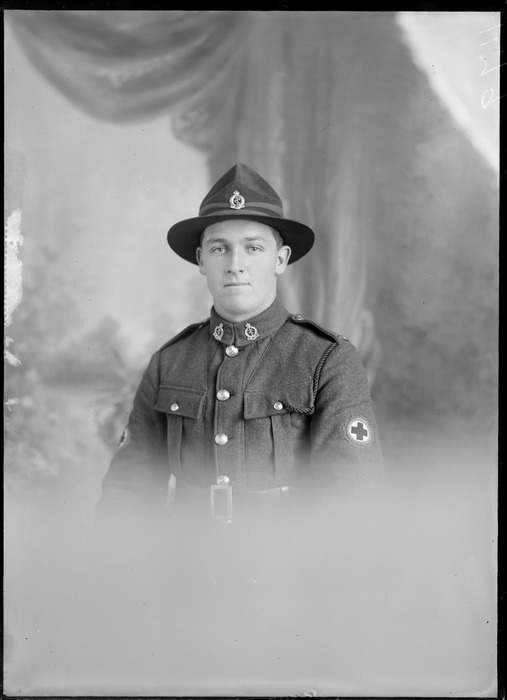 Studio upper torso portrait of an unidentified man dressed in a Medical Corps army uniform, showing the Red Cross badge on his left upper arm, with two badges on the lapels of his jacket, with a pin on his hat, possibly Christchurch district