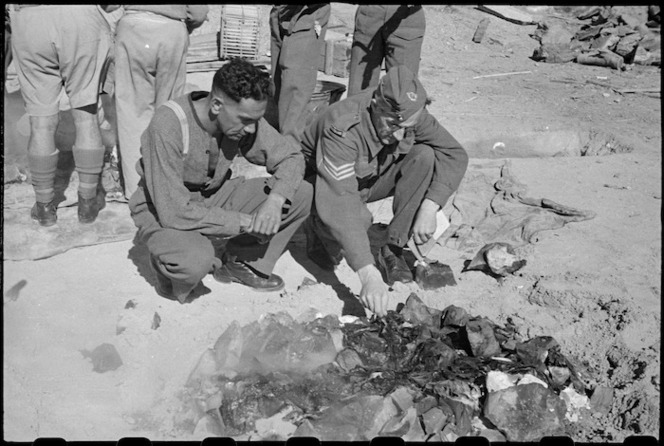 Members of the 28th (Maori) Battalion with uncovered hangi at Maadi Camp on Christmas Day, Egypt - Photograph taken by George Robert Bull