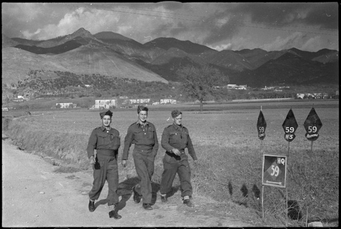 Soldiers walking near black diamond signs of the NZ Division in the Volturno Valley, Italy, World War II - Photograph taken by George Kaye