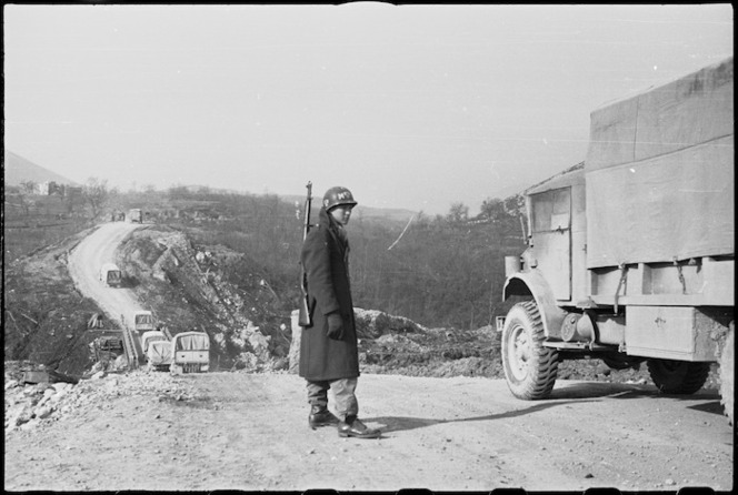 American MP directing NZ traffic at temporary bridge on the 5th Army Front in southern Italy, World War II - Photograph taken by George Kaye