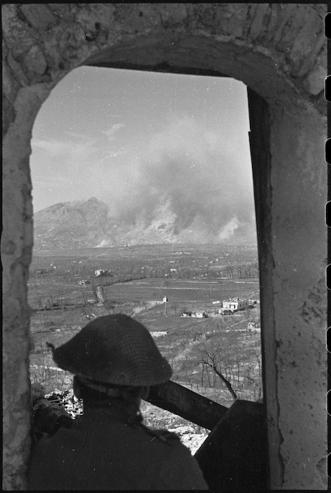 New Zealand observer silhouetted against the Monte Cassino battle area, Italy, World War II - Photograph taken by George Kaye