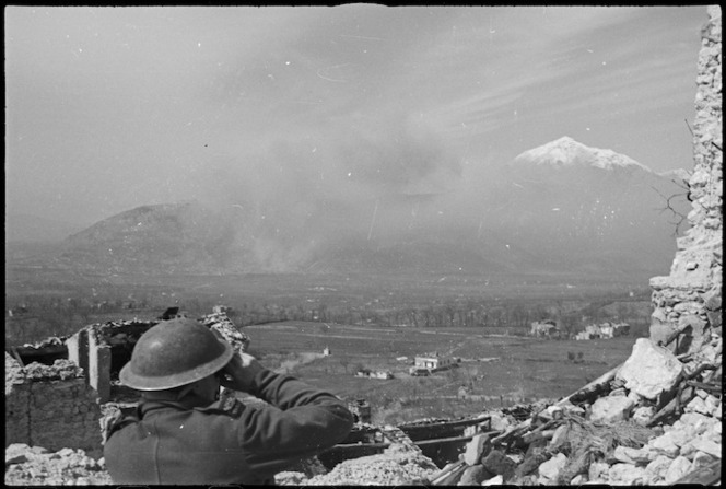 A New Zealander observing the combined bombing and shelling attack on Cassino, Italy, World War II - Photograph taken by George Kaye