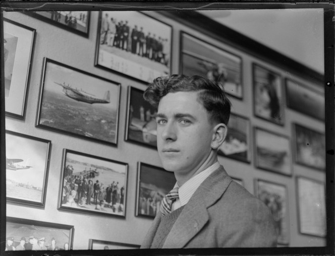 Portrait of D C Morris, Musick Point, Auckland region, in front of wall of framed photographs