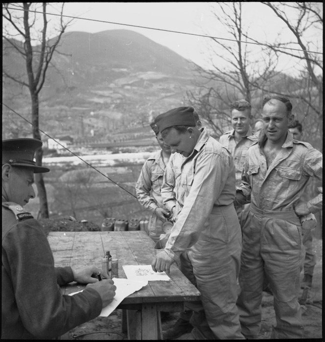 Corporal R Stark takes a Mepacrine antimalarial tablet under the supervision of Major H T Knights, Italy, World War II - Photograph taken by M D Elias
