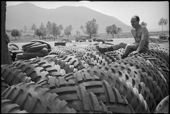 T Ford rests on some of the large tyres for 2 NZ Division vehicles on the Cassino Front, Italy, World War II - Photograph taken by George Kaye
