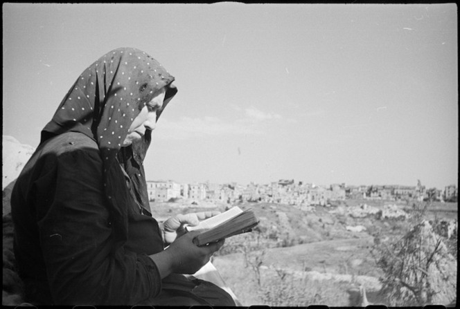 Italian peasant woman reading a bible with the ruins of Orsogna in background, Italy, World War II - Photograph taken by George Kaye