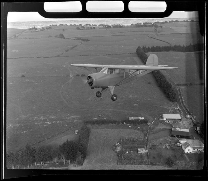 Rearwin Sportster aeroplane ZK-AKF, in flight over a rural area, Auckland Region