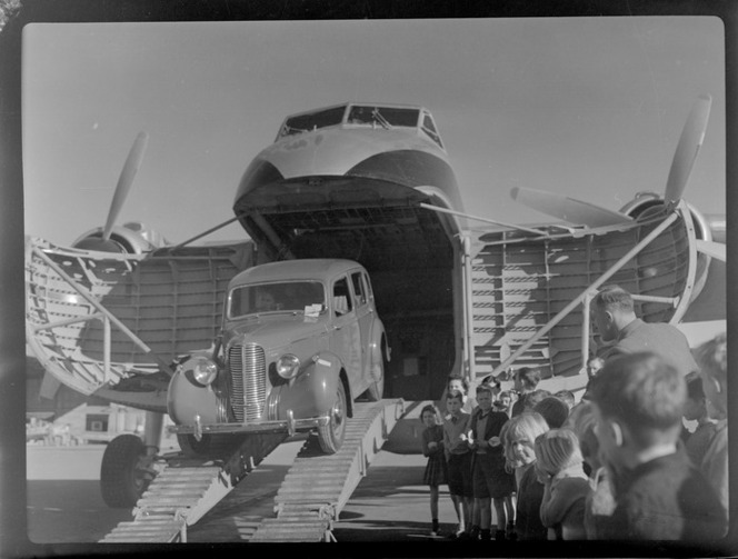 Bristol Freighter Tour, view of an unidentified man unloading a car off Bristol Freighter transport plane 'Merchant Venturer' G-AIMC with children looking on, Harewood Airport, Christchurch City. Whites Aviation Ltd :Photographs. Ref: WA-08507-G.