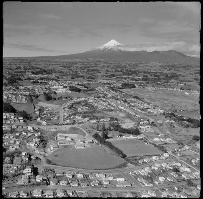 View over the New Plymouth City suburb of Lynmouth with Devon Intermediate School and St Joseph's Primary Schools to Taranaki Base Hospital, with farmland and Mount Taranaki beyond