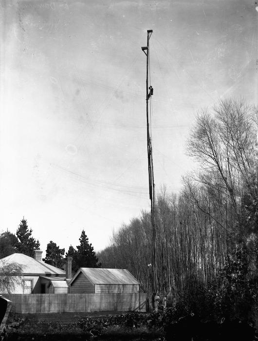 Melvin Vaniman climbing a pole to take a photograph, Belfast, Canterbury