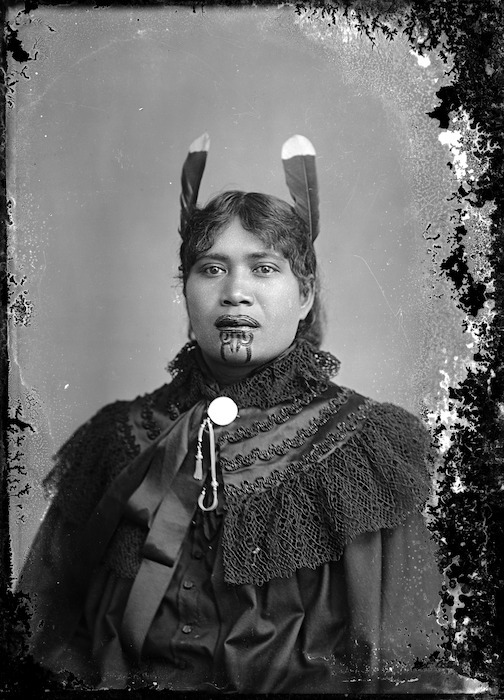 Unidentified Maori woman with a chin moko, feathers in her hair, and European clothing