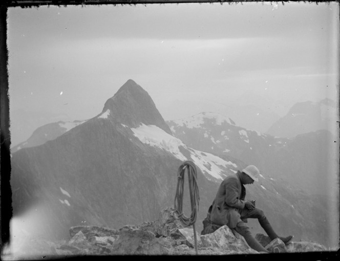 [Jack Murrell] sitting on Mount Wilmur with Mount Kepka in background, during Edgar Williams and Jack Murrell's climbing expedition in the Southern Alps, Fiordland National Park