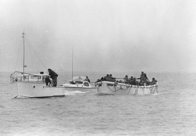 Survivors from the Wahine shipwreck in a lifeboat, being tugged by two boats, Wellington