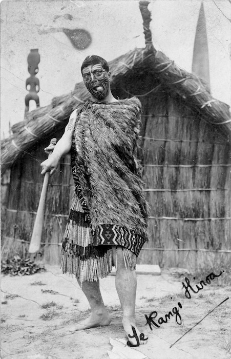 Peter Henry Buck wearing traditional Maori clothing, wielding a wooden weapon