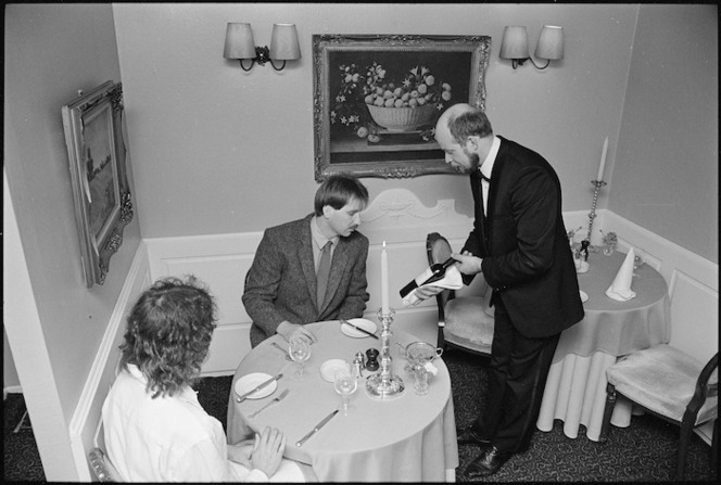 Philip Temple, Orsini's proprietor, presenting a bottle of wine to a customer - Photograph taken by Ray Pigney